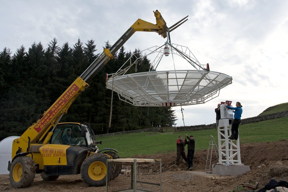 Radiotelescopio SPIDER 500A installato in Scozia: con l'aiuto di una macchina per il sollevamento, l'antenna viene installata sulla montatura